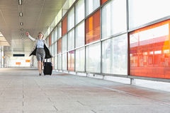 Full length of young businesswoman with luggage rushing in railroad station Stock Image