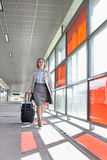 Full length of young businesswoman with luggage walking in railroad station Royalty Free Stock Photo