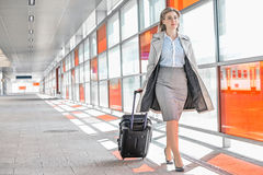 Full length of young businesswoman with luggage walking in railroad station Royalty Free Stock Photos