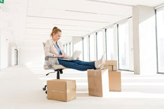 Full length of young businesswoman using laptop with feet up on cardboard box in new office Royalty Free Stock Image
