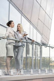 Full length of young businesswomen conversing at office balcony Stock Photo