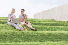 Full length of young businesswomen with disposable coffee cup and laptop sitting on grass steps against sky Royalty Free Stock Image