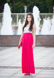 Full length of young caucasian female with long red skirt standing in front of a fountain outdoor Stock Images