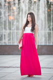 Full length of young caucasian female with long red skirt standing in front of a fountain outdoor. Romantic portrait of the woman with long hair with fountain stock photography