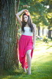 Full length of young caucasian female with long red skirt standing near the tree outdoor. Romantic portrait of the woman in the forest Stock Photos