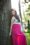 Full length of young caucasian female with long red skirt standing near the tree outdoor. Romantic portrait of the woman in the forest Royalty Free Stock Image