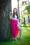 Full length of young caucasian female with long red skirt standing near the tree outdoor. Romantic portrait of the woman in the forest Stock Image