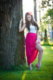 Full length of young caucasian female with long red skirt standing near the tree outdoor. Romantic portrait of the woman in the forest Stock Photo