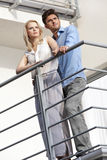 Full length of young couple looking away while standing at balcony Royalty Free Stock Photo