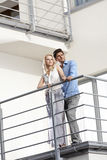 Full length of young couple looking away while standing at hotel balcony Royalty Free Stock Photography