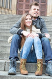 Full length of young couple sitting on steps outdoors Stock Photos