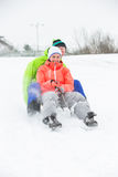 Full length of young couple sledging on snow covered land Royalty Free Stock Image