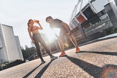 Hydrating. Full length of young couple in sport clothing having a pause to drink water while exercising outdoors Royalty Free Stock Images
