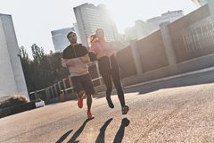 Best jog ever. Full length of young couple in sport clothing running through the city street together Stock Photos