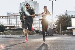 Making effort. Full length of young couple in sport clothing running through the city street together Royalty Free Stock Photos
