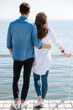Full length of a young couple standing backwards hugging Stock Photography