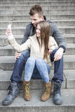 Full length of young couple taking picture of themselves while sitting on steps outdoors Stock Photo