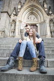 Full length of young couple taking selfie while sitting on steps outdoors Stock Image