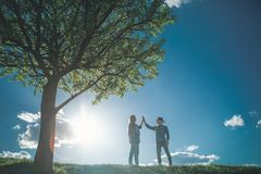 Boy and girl falling in love on meadow. Full length of young couple walking in bright sunny day. They are standing by nice green tree opposite to each other and Stock Image