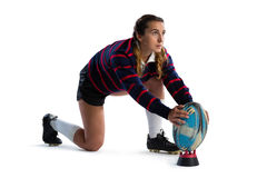 Full length of young female athlete keeping rugby ball on tee Royalty Free Stock Photo