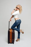 Full length of young female in casual standing with travel suitcase Royalty Free Stock Image