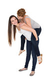 Full length of a young female piggybacking friend Stock Photo