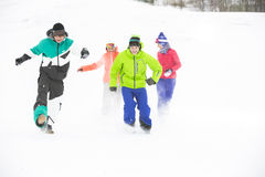 Full length of young friends having fun in snow Royalty Free Stock Photos