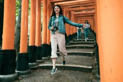 Girl cheerfully jumping down stair under red gate royalty free stock photo