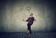Full length of a young guy juggling a football. On a gray wall background royalty free stock photography