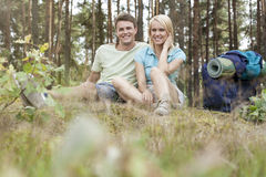 Full length of young hiking couple with backpack relaxing in forest Stock Image