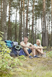 Full length of young hiking couple with backpacks relaxing in forest Royalty Free Stock Photography