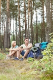 Full length of young hiking couple with backpacks relaxing in forest Royalty Free Stock Photo
