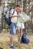 Full length of young hiking couple reading map in forest Royalty Free Stock Images