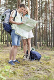 Full length of young hiking couple reading map in woods Royalty Free Stock Images