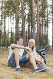 Full length of young hiking couple relaxing in forest Royalty Free Stock Photography