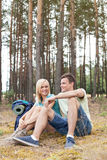Full length of young hiking couple relaxing in forest Stock Images