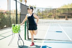 Female tennis player stretching on court. Full length of young hispanic sporty woman exercising stretching legs before training on tennis court Royalty Free Stock Photography