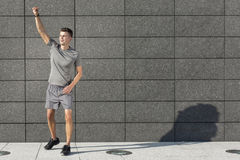 Full length of young jogger with clenched fist standing against tiled wall Royalty Free Stock Photo