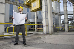Full length of young male architect with blueprint outside industry Royalty Free Stock Photography