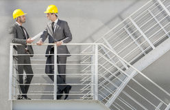 Full length of young male architect discussing on stairway Royalty Free Stock Image