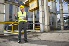 Full length of young male architect gesturing outside industry Stock Photo