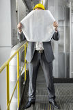 Full length of young male architect holding blueprint in front of face at industry Stock Photography