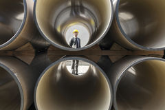 Full length of young male architect through stacked pipes at construction site Stock Photo