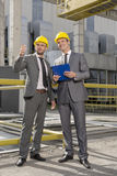 Full length of young male architects with clipboard discussing outside industry Royalty Free Stock Photo