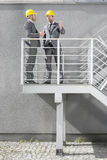 Full length of young male architects communicating on stairway Stock Photography