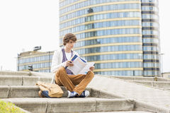 Full length of young male college student reading book against building Royalty Free Stock Photography