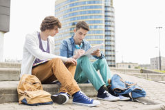 Full length of young male college students studying on steps against building Stock Image