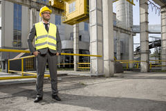 Full length of young male engineer with hands in pockets standing outside industry Royalty Free Stock Photography