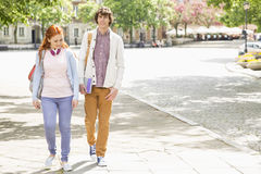 Full length of young male and female college students walking on footpath Royalty Free Stock Photos