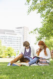 Full length of young male and female friends studying at college campus Royalty Free Stock Photo